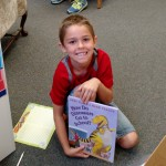 boy showing off his dinosaur book